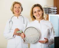 Zwei Ärztinnen, die Zeit in der Uhr zeigen Lizenzfreies Stockbild