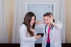 Zwei Ärztinnen oder Krankenschwestern betrachten die Tablette, ist man entsetzt oder überrascht sehr lizenzfreies stockfoto