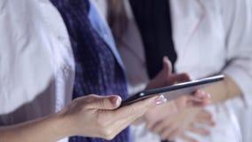 Zwei Ärztinnen schauen durch medizinische Anmerkungen in einer Datei und beraten sich auf Diagnose Intelligentes Berufsgesundheit stock video