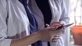 Zwei Ärztinnen schauen durch medizinische Anmerkungen in einer Datei und beraten sich auf Diagnose Intelligentes Berufsgesundheit stock video footage