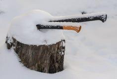 Zwei Äxte gehaftet in einem Stumpf bedeckt mit Schnee stockbilder