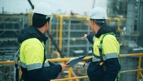 Zwei Öl- und Gasarbeitskräfte, die an der Raffinerieindustrie duscussing sind stock footage