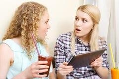 Zwei überraschte Mädchen mit Tablette im Café Lizenzfreies Stockbild