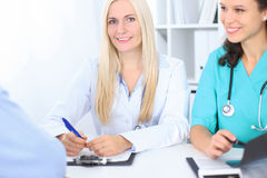 Zwei überzeugte freundliche Ärztinnen, die am Tisch sitzen und hören auf Patienten Fokus auf blonder Ärztin Lizenzfreies Stockbild