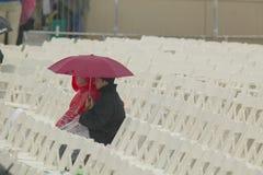 Zwei Abbildungen, die Regenschirme anhalten, sitzen unter Reihen der Stühle, welche die Eröffnungsfeiern der Clinton-Präsidentenb Stockfotos