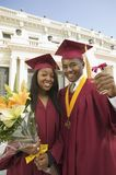 Zwei Absolvent, die Diplom und Blumen anhalten Lizenzfreies Stockfoto