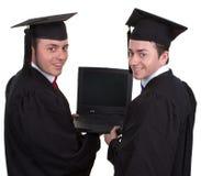 Zwei Absolvent, die einen Laptop herum schaut, lokalisiert auf Weiß halten Stockbilder