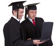 Zwei Absolvent, die zusammen an einem Laptop, lokalisiert auf Weiß arbeiten Lizenzfreie Stockbilder