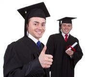 Zwei Absolvent mit der ersten Vertretung Daumen up Zeichen und das Se Stockbild