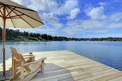 Zwei adirondack Holzstühle mit Regenschirm auf dem Dock, das blauen See gegenüberstellt Lizenzfreies Stockbild