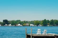 Zwei Adirondack Stühle auf einem Dock Stockfotos