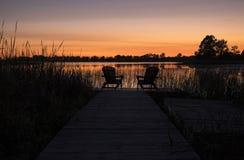 Zwei Adirondack-Stühle durch das Dock nach Sonnenuntergang Lizenzfreies Stockfoto