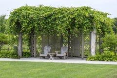 Zwei Adirondack-Stühle unter einem Trauben-Gitter Stockfotos