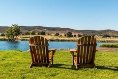 Zwei Adirondack-Stühle vor einem ländlichen See Lizenzfreie Stockfotografie