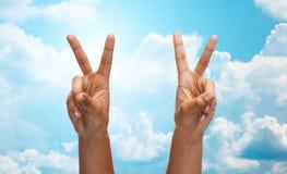 Zwei afrikanische Hände, die Sieg- oder Friedenszeichen zeigen Stockfotografie