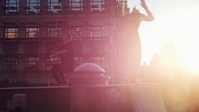 Zwei akrobatische Männer springen weg vom Stand - Sonnenuntergang stock footage