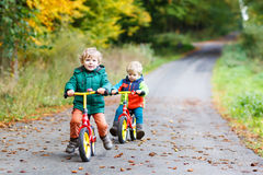 Zwei aktive Bruderjungen, die Spaß auf Fahrrädern im Herbstwald haben Lizenzfreies Stockbild