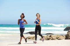 Zwei aktive junge Frauen, die auf dem Strand laufen Lizenzfreie Stockbilder