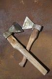 Zwei alte Äxte auf einer rostigen Blechtafel Stockfotos