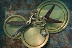 Zwei alte antike Scheren mit den Goldgriffen, eingefügt in einander durch Ringe auf gelben kupfernen Tellern, ein Symbol der Komm Lizenzfreie Stockbilder