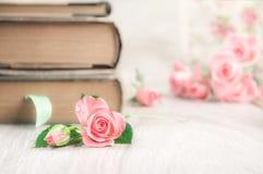 Zwei alte Bücher auf Holztisch unter recht kleinen rosa Rosen, te Stockbilder