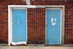 Zwei alte blaue Tür-Einfassung durch Brickwork Lizenzfreies Stockbild