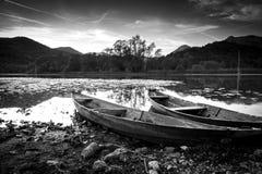 Zwei alte Boote auf dem Ufer von einem See mit Bäumen im Hintergrund in einer Schwarzweiss-Fotografie Lizenzfreies Stockfoto