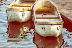 Zwei alte Boote am Pier, gelber Fotofilter Stockfotografie