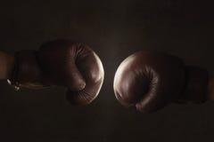 Zwei alte braune Boxhandschuhe zusammen geschlagen Stockfoto