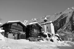 Zwei alte Chalets und eine Kapelle im Schnee Stockbild