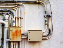 Zwei alte elektrische Kästen installierten und verteilten das Stromkabel über alte Edelstahlrohrlinien auf weißem Beton mit Kopie Stockbild