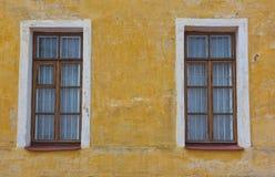 Zwei alte Fenster auf der gelben Wand Lizenzfreies Stockfoto