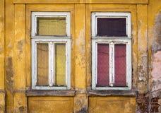 Zwei alte Fenster auf einem gelben Haus Stockfotos