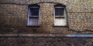 zwei alte Fenster auf einer Ziegelsteinmaurerarbeit stockbild