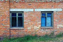 Zwei alte Fenster hinter einem Gitter auf einer Backsteinmauer Stockbilder