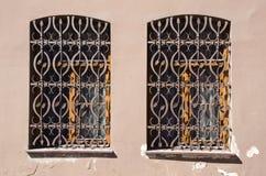 Zwei alte Fenster mit Metallvergitterungen Lizenzfreie Stockfotografie