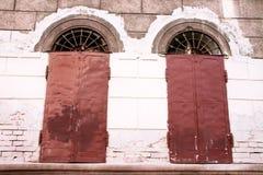 Zwei alte Fenster mit orange Fensterläden Lizenzfreie Stockbilder