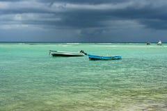 Zwei alte Fischerboote im klaren Meer mit einem stürmischen Hintergrund Stockfoto