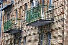 Zwei alte grüne Balkone auf der Backsteinmauer des Hauses Stockfotografie