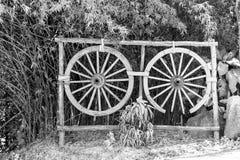 Zwei alte hölzerne Räder auf hoher Buschanlage Lizenzfreies Stockbild