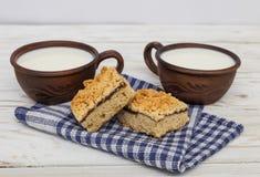 Zwei alte keramische Schalen Milch und zwei Stücke der zerriebenen Torte Lizenzfreie Stockfotografie