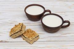 Zwei alte keramische Schalen Milch und zwei Stücke der zerriebenen Torte Lizenzfreies Stockbild