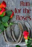 Zwei alte Pferdeschuhe zusammengepaßt mit roten Rosen der Seide auf verkratzt herauf Stahlhintergrund lizenzfreie stockfotografie