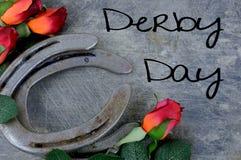 Zwei alte Pferdeschuhe zusammengepaßt mit roten Rosen der Seide auf verkratzt herauf Stahlhintergrund stockbild