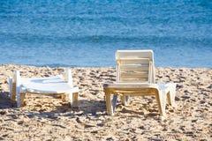 Zwei alte sunloungers auf tunesischem Strand Lizenzfreie Stockfotos
