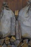 Zwei alte Taschen hergestellt auf Woodpile mit Feuerholz Lizenzfreie Stockfotos