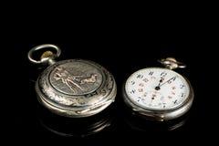 Zwei alte Taschenuhren auf einer schwarzen reflektierenden Oberfläche Stockfoto