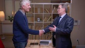 Zwei alte Teilhaber halten Erschütterungshänden auf dem Bücherregalhintergrund stand, der ein Abkommen gemacht wird stock video footage