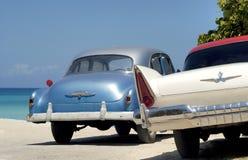 Zwei alte Weinleseautos am Strand in Kuba Stockfotografie
