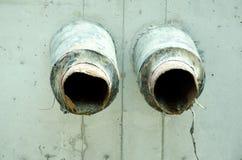 Zwei altes Abwasser oder Wasserleitungen nehmen vom Betonblock im Boden heraus Stockfotos